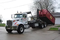 Image of truck dropping off dumpster.